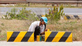 Man painting roadworks barriers on a road in Vietnam Royalty Free Stock Photos