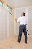Man painting room with roller. Attached to an extension pole stock image