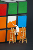 Man painting the squares on a rubiks cube Royalty Free Stock Images