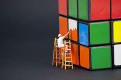 Man painting the squares on a rubiks cube Stock Photography