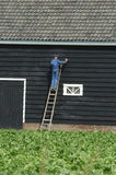 A man is painting tar on this house. Stavenisse, Zeeland, The Netherlands 06-Februari-2006: A traditional house. A man is painting tar on this house Royalty Free Stock Photos