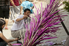 Man Painting Torch. An Yi Chinese man paints a torch that will later be filled with fireworks and lit on fire for the annual Torch Festival in Yunnan province Stock Image