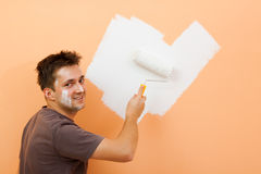 Man painting a wall. A smiling man painting the orange wall Royalty Free Stock Photo
