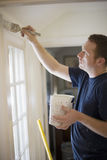 Man painting wall. Young man painting door trim inside a house Royalty Free Stock Photo