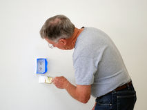Man painting a wall. A senior man painting the area near a socket in the wall Stock Photos