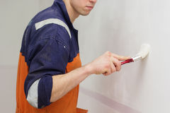 Man is painting wall with brush Royalty Free Stock Photo