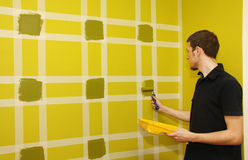 Man painting wall with masking tape Stock Photography
