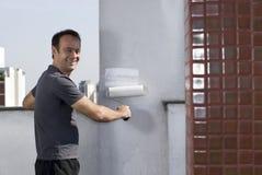 Man Painting Wall Smiling - Horizontal Stock Images