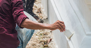 A man painting the wall. A man painting a wall in white Royalty Free Stock Images
