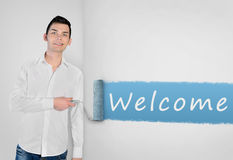 Man painting Welcome word on wall Stock Image