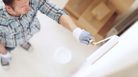 Man painting with white paint stock video