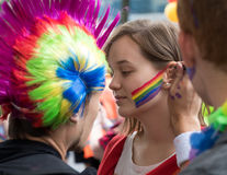 Man painting on a woman`s face during Prague Pride. PRAGUE, CZECH REPUBLIC - AUGUST 12, 2017: Man painting a rainbow on a woman`s face during Prague Pride - a Royalty Free Stock Images