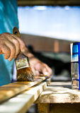 Man painting wood with lacquer natural color. Stock Photography