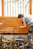 Man is painting wooden boards with a foam roller Royalty Free Stock Image
