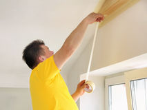 Man Applying the Painting Tape Royalty Free Stock Photography