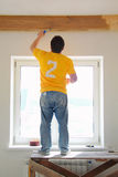 Man Painting a Exposed Beams. A man painting a wooden ceiling exposed beams royalty free stock image