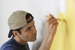 Man Painting Yellow Color On Wall Stock Images