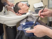 A man paints his hair in a Barber shop. Innovative technologies of hair restoration for men. royalty free stock image