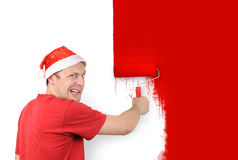 The man paints a wall roller brush with a red Stock Image