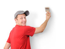 The man paints a withe wall with a brush. On withe background Stock Photo