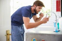 Man In Pajamas Brushing Teeth And Using Mobile Phone Stock Photos