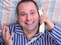 Man in pajamas calls from the phone in bed Royalty Free Stock Image