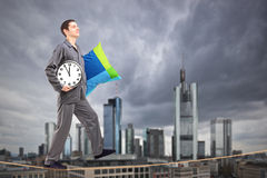 Man holding a pillow and clock sleepwalking on a rope, with Fran Stock Photography