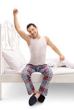 Man in pajamas sitting on a bed and stretching himself Stock Photo