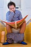 Man in pajamas sitting on the toilet Stock Photo