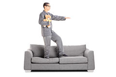 Man in pajamas sleepwalking on sofa Stock Photo