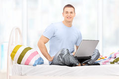 Man in pajamas working on a laptop seated on a bed Stock Images