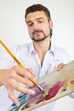 Man with palette. Focused on the hand and brush. Painter with brush and palette Royalty Free Stock Photography