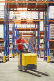 Man With Pallet Jack Through Warehouse. Blurred man driving pallet jack through warehouse Royalty Free Stock Photography
