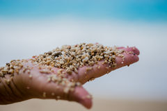 Man palm holding pebble  and sand. Man open hand holding pebble and sand of mixed white biege and terracotta color shot on Kaputash beach of Turkey with focus on Royalty Free Stock Photos