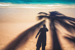 Man and palm tree shadows on tropical beach Royalty Free Stock Photography