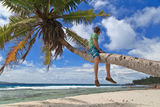 Man on palm in tropical beach Royalty Free Stock Photo