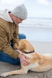 Man pampering dog while sitting. At the beach Stock Images