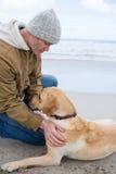 Man pampering dog while sitting Stock Images