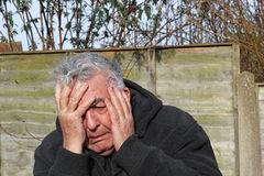 Man panic attack. Close up of a senior man with his hands to his face having a panic attack. Very anxious and scared Royalty Free Stock Photos