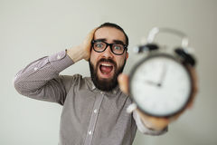 Man in panic holds alarm clock and head in fear of deadline Stock Image