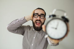 Man in panic holds alarm clock and head in fear of deadline Royalty Free Stock Photography