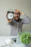 Man in panic holds alarm clock and head scared of deadline Royalty Free Stock Images