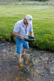 Man Panning For Gold. Middle aged man panning for gold in a clear mountain stream at a mining days celebration in South Pass, Wyoming Royalty Free Stock Image