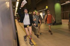 A man without pants running in the metro station during the Stock Photography