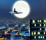 Man on paper airplane above the city Stock Photography