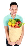 Man with paper bag full of fruits and vegetables Royalty Free Stock Photography