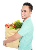 Man with paper bag full of fruits and vegetables Royalty Free Stock Photo