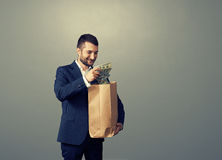 Man with paper bag and money over dark Royalty Free Stock Photos