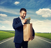 Man with paper bag and money Stock Image