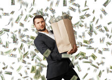 Man with paper bag under dollar's rain Royalty Free Stock Photography